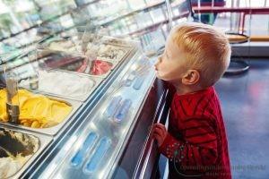 Kind kijkt verlangend naar lekkers in de winkel